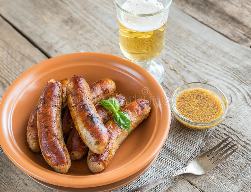 Grilled sausages with glass of beer. Grilled sausages with mustard sauce and glass of beer royalty free stock photos