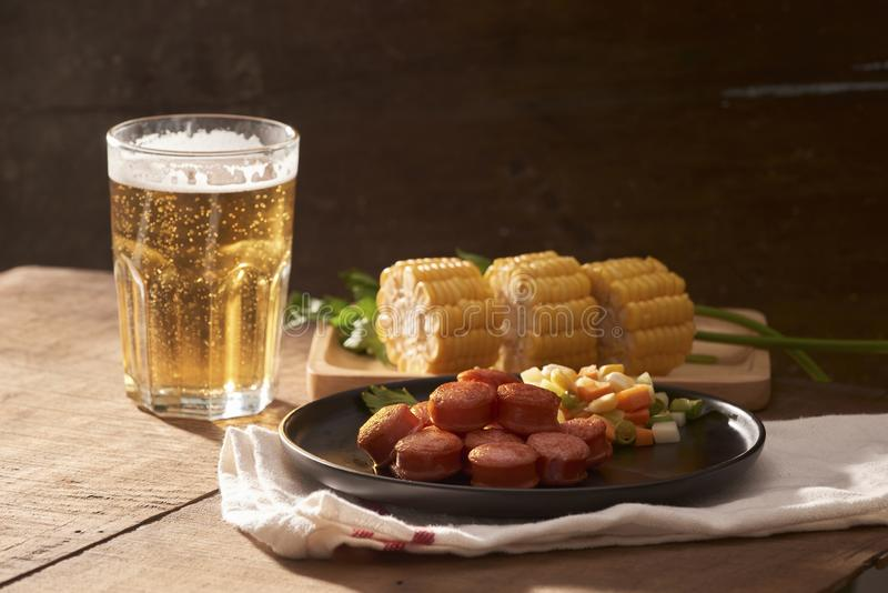 Grilled sausages with glass of beer on wooden table with copy sp royalty free stock photo