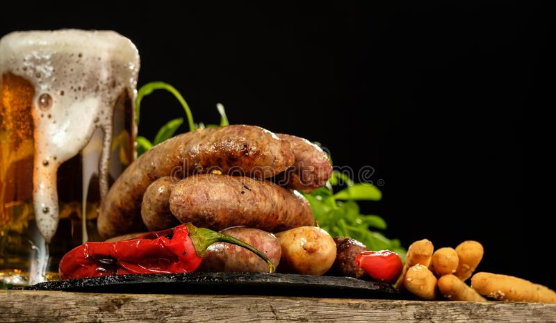Grilled sausages with a glass of beer on a wooden table royalty free stock image