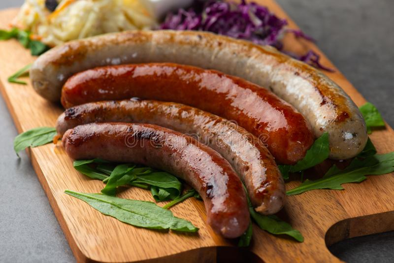Grilled sausages with mash potatoes on wooden board royalty free stock image