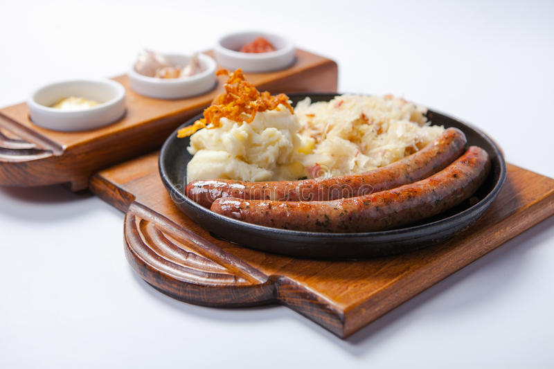 Grilled sausages, and potatoes on cooking pan royalty free stock images