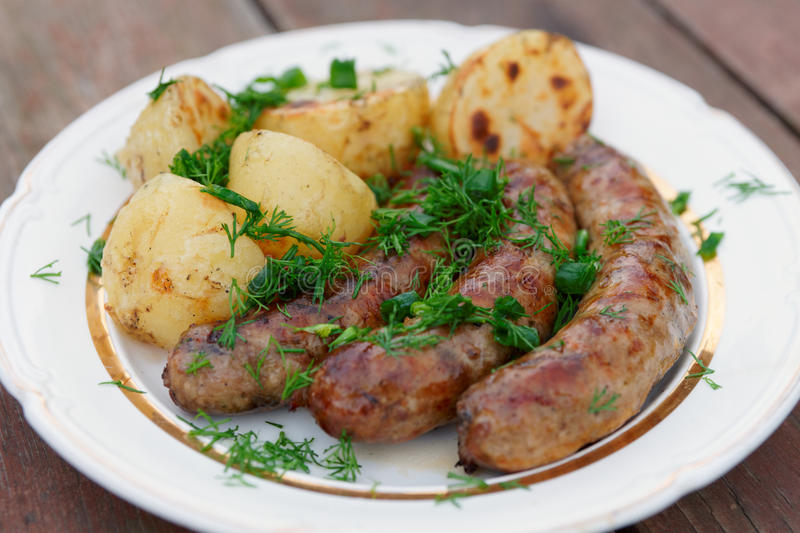 Grilled sausages and potatoes stock images