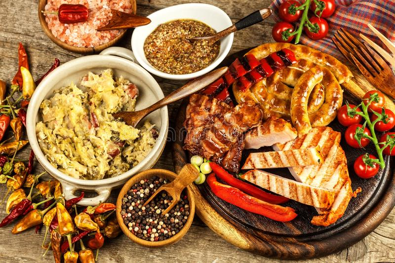 Grilled sausages spiral served on rustic round cutting board with mustard. Homemade barbecue. Food preparation. Stewed cabbage stock photos