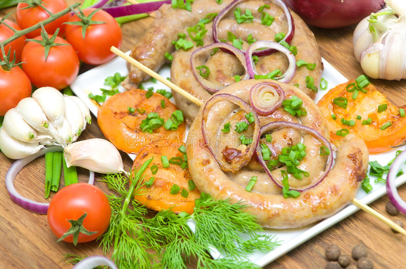 Grilled sausages and vegetables close-up. horizontal photo. Grilled sausages with roasted tomatoes and vegetables close-up. horizontal photo stock image