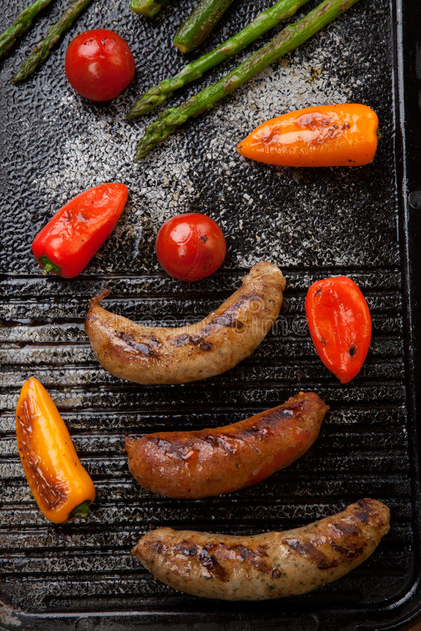 Grilled Sausages and Vegetables stock images