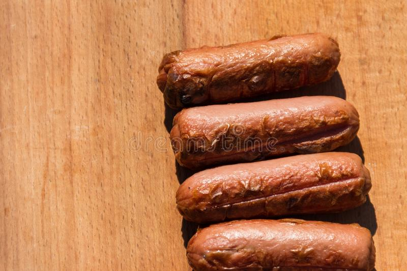 Grilled sausages on wooden board royalty free stock photo