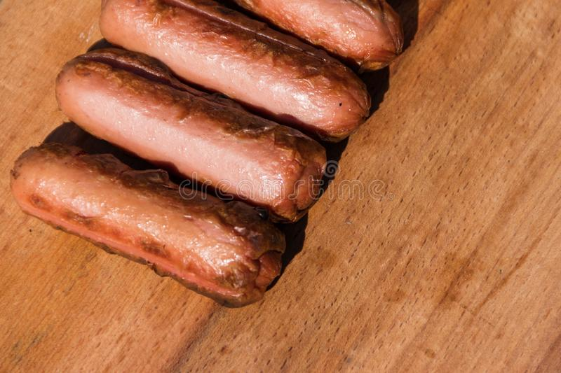Grilled sausages on wooden board royalty free stock images