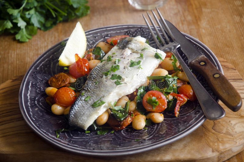 Grilled sea bass. Sea bass with chorizo, tomatoes and butter beans stock images