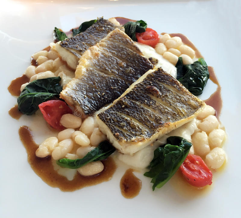 Grilled Sea Bass Fillet. With chickpea, tomatos stock image