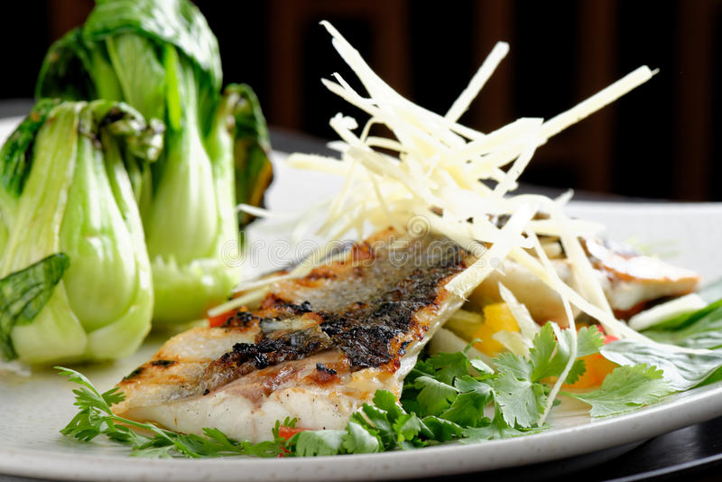 Grilled sea bass fillet with ginger and Pak Choy stock photos