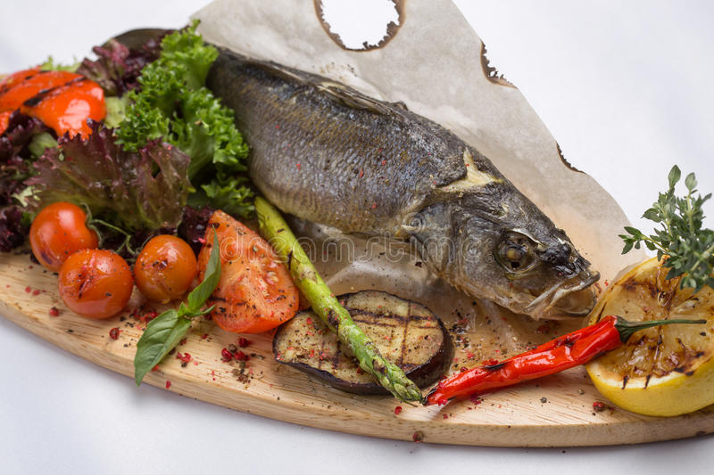 Grilled sea bass fish. With asparagus and ingredients isolated on white background royalty free stock images
