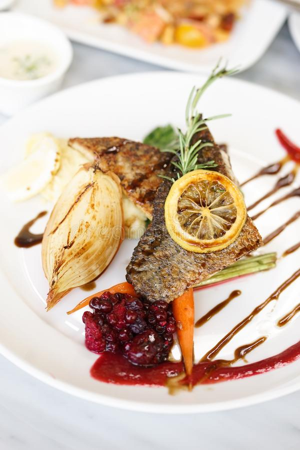 Grilled Sea Bass. Fish steak of a grilled sea bass served with raspberry sauce and sided vegetables. stock images