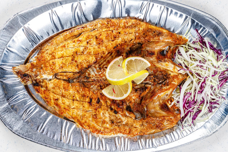 Grilled sea bream fish on foil plate served with lemon and cauliflower royalty free stock images