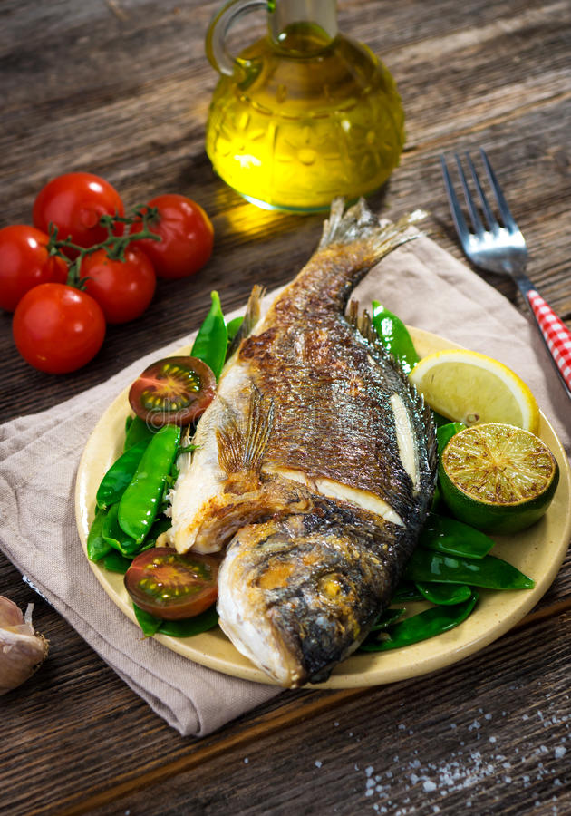 Grilled sea bream fish. On wooden background stock images