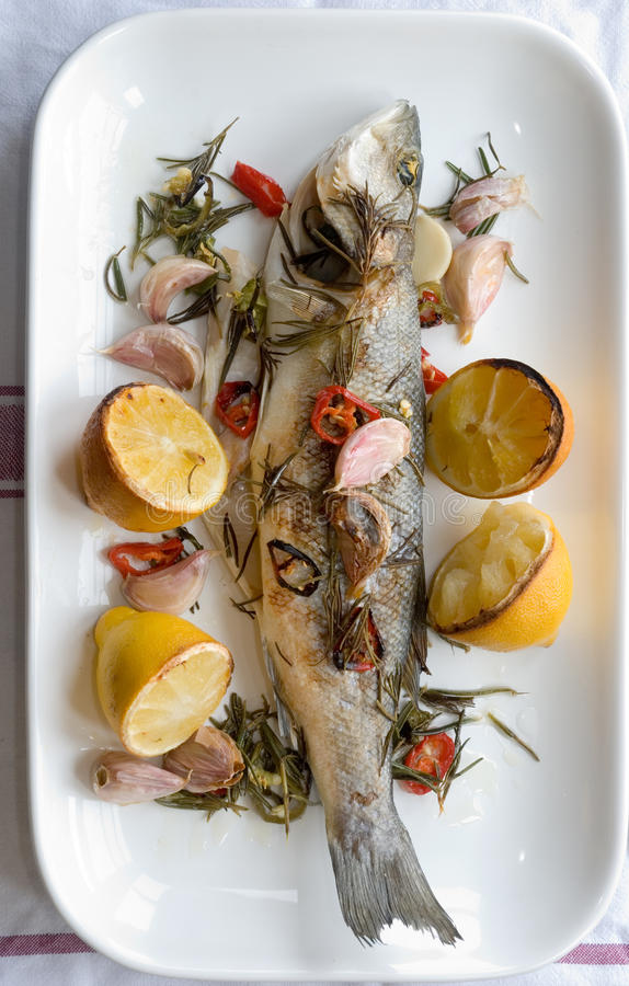 Grilled seabass. With lemon rosemary and garlic stock images