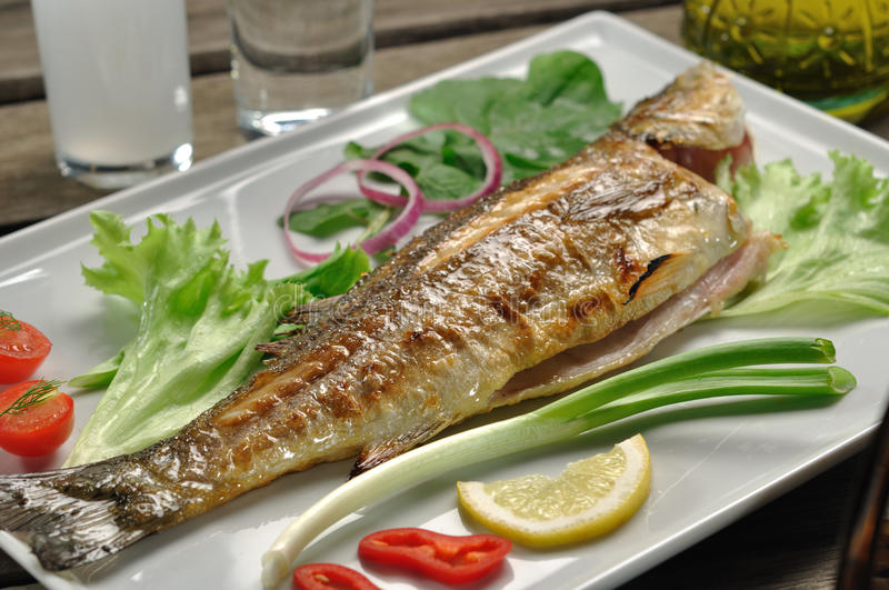 Grilled seabass. Served with onion and some different garnish stock photography