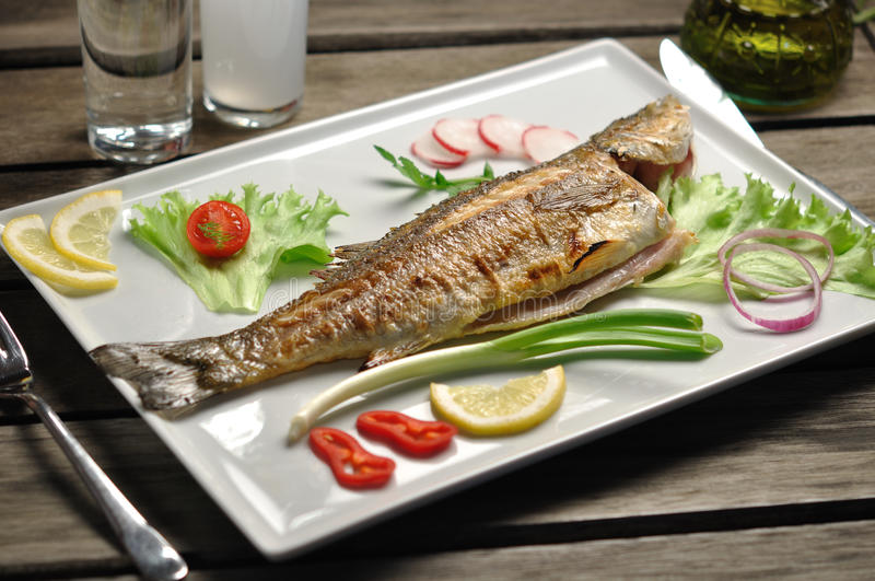 Grilled seabass. Served with some different garnish and traditional greek drink ouzo royalty free stock photo