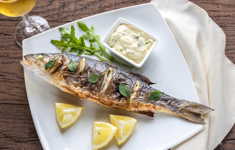 Grilled seabass on the plate. Grilled seabass on the square plate close up royalty free stock photos
