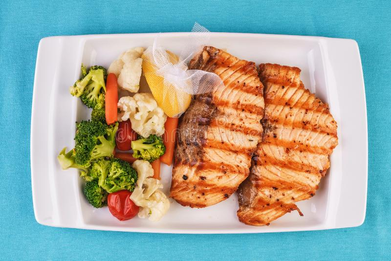Grilled seafood. Salmon fish steak with greens, broccoli, cauliflower, carrots, cucumber, lemon and chili. stock photography