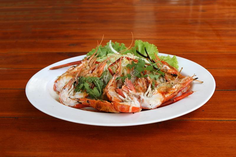 Grilled shrimp and cut in half with vegetables and cabbage in white dish. stock image