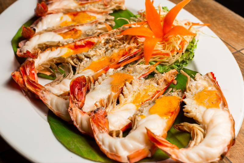 Grilled shrimp with Shrimp Paste in white dish showing the delicious Shrimp Paste inside its shell on wood table. Thai seafood. royalty free stock images