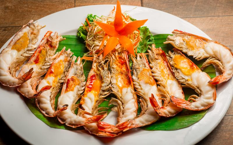 Grilled shrimp with Shrimp Paste in white dish showing the delicious Shrimp Paste inside its shell on wood table. Thai seafood. stock photography