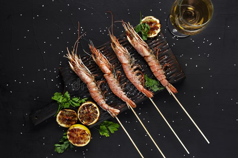 Grilled shrimp skewers. Seafood, shellfish. Shrimps Prawns skewers with herbs, garlic and lemon on black stone royalty free stock photos