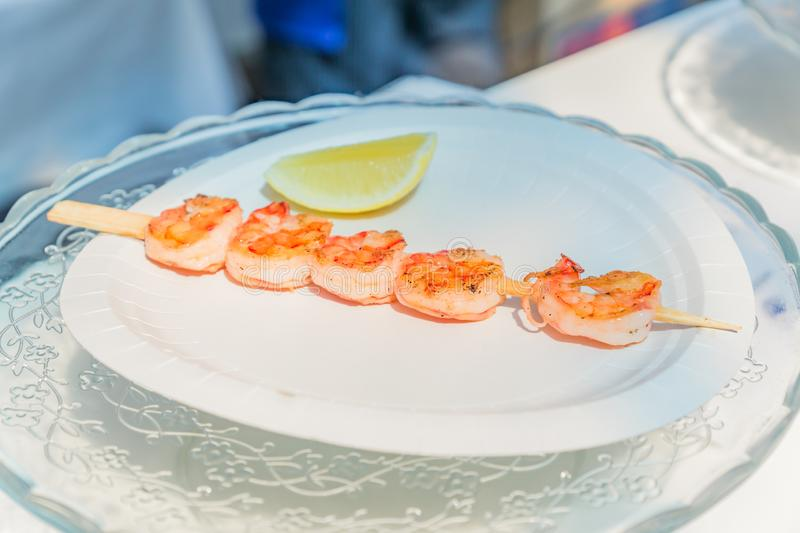 Grilled shrimp skewers served with lemon slice on white plate. Street food festival. Seafood style royalty free stock image