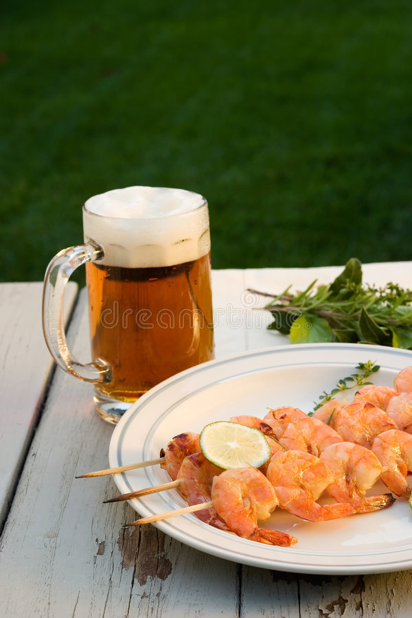 Grilled shrimps and beer outside royalty free stock photo