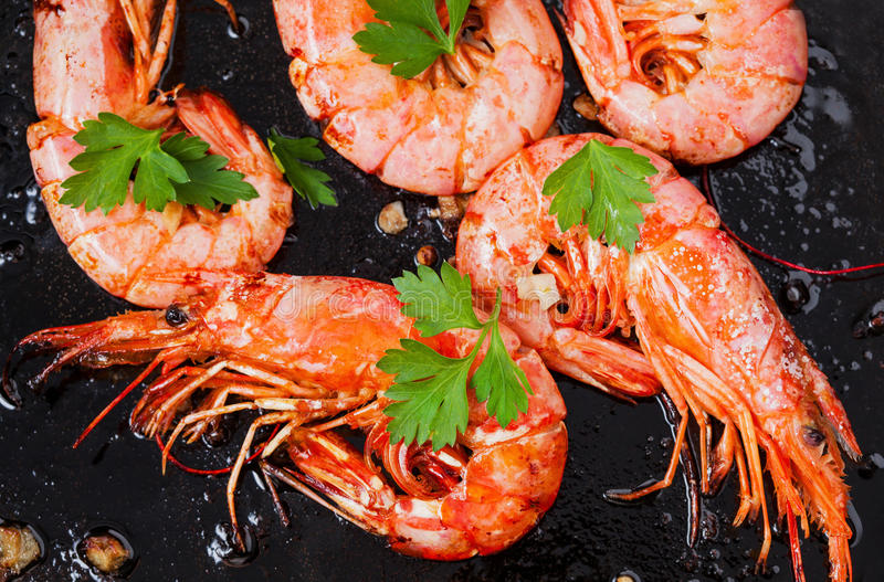 Grilled shrimps on black background. Delicious seafood appetizer served boiled or grilled with spices. Close up. stock photography