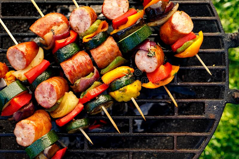 Grilled skewers of meat, sausages and various vegetables on a grill plate, outdoors, top view. royalty free stock photos