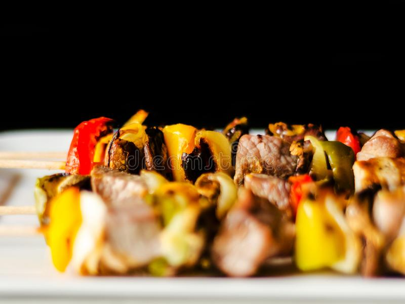 Grilled skewers of meat and vegetables on a wooden board, colorful and tasty dish royalty free stock photos