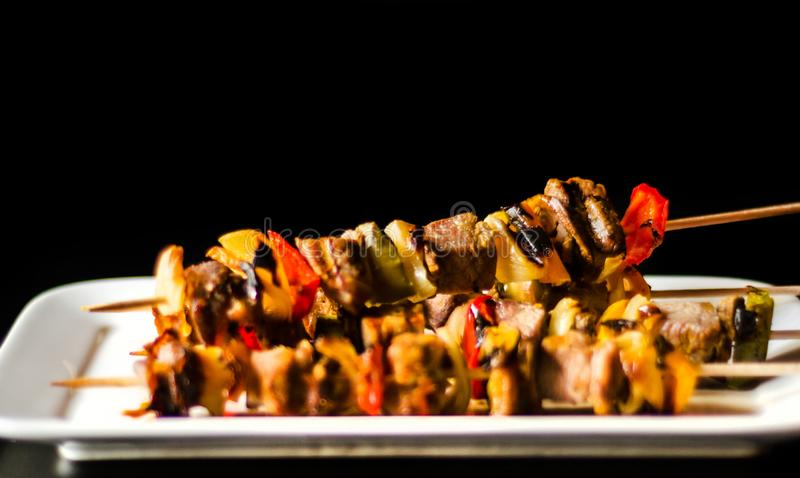 Grilled skewers of meat and vegetables on a wooden board, colorful and tasty dish royalty free stock image