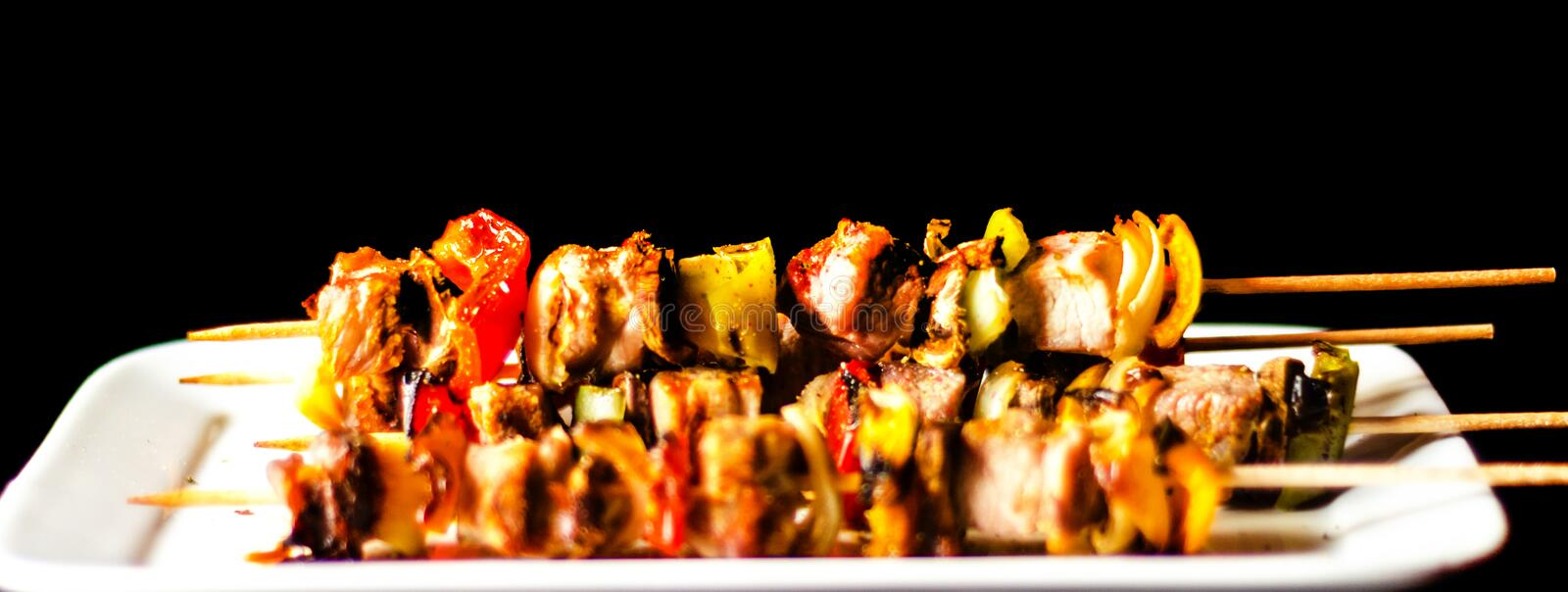 Grilled skewers of meat and vegetables on a wooden board, colorful and tasty dish stock photo