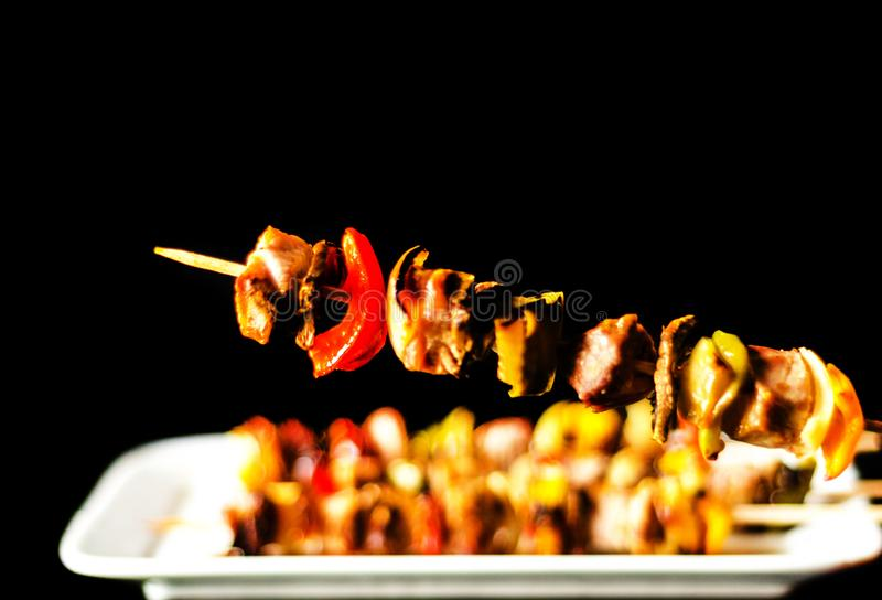 Grilled skewers of meat and vegetables on a wooden board, colorful and tasty dish royalty free stock photo