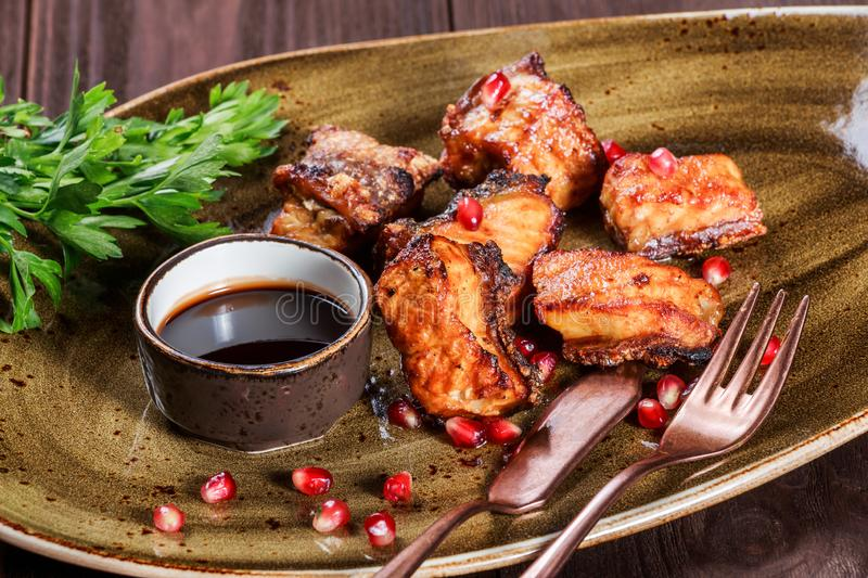 Grilled sliced fish with pomegranate sauce and spice on plate on table. Healthy food stock photo