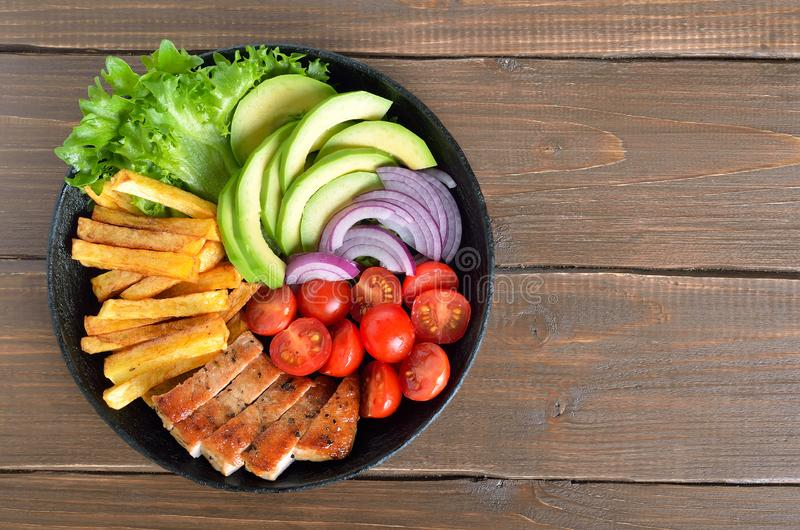 Grilled sliced pork steak with potatoes, tomatoes and avocados royalty free stock images