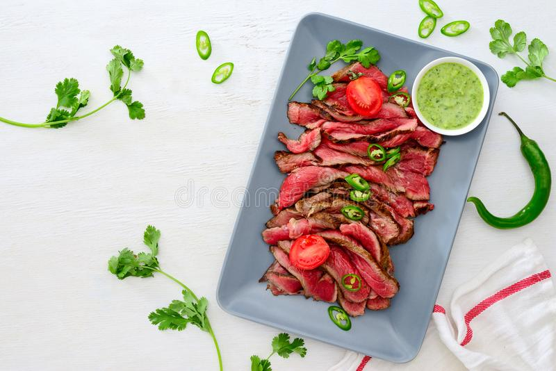 Grilled and sliced rare beef skirt steak served with green chimichurri sauce royalty free stock image
