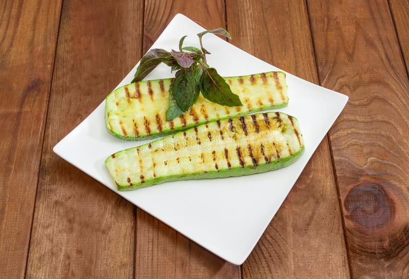 Grilled sliced vegetable marrow on square dish on rustic table. Grilled long slices of vegetable marrow decorated with fresh basil sprig on the square white dish royalty free stock photo