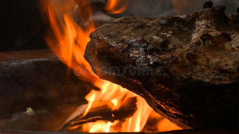 Grilled and smoked pork thigh on professional grill. Grilling Prague ham with bornfire royalty free stock photography