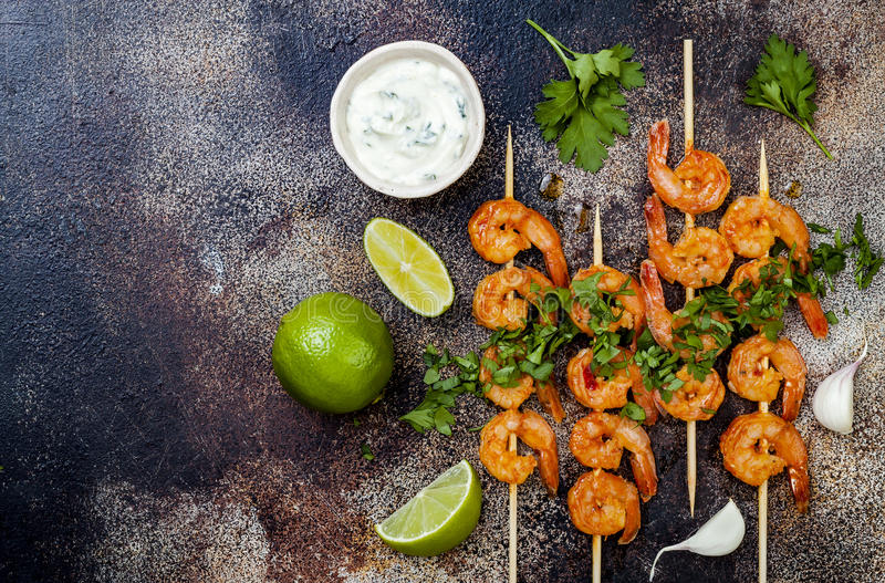 Grilled spicy lime shrimp skewers with creamy avocado garlic cilantro sauce. Top view, overhead, flat lay, copy space. royalty free stock photos