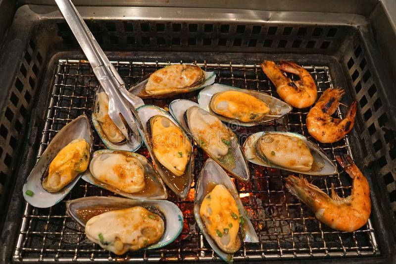 Grilled spicy sauce mussel and shrimp on hot stove royalty free stock images