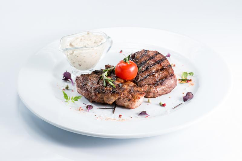 Grilled steak delicious beef meat. On a white plate royalty free stock images
