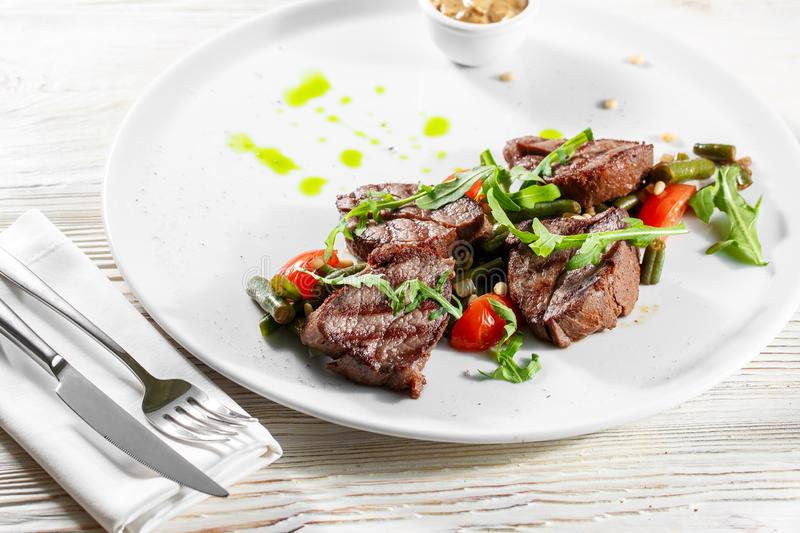 Grilled steak delicious beef meat on a white plate on a light background menu.  royalty free stock photos