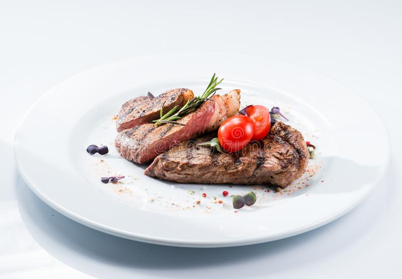Grilled steak delicious beef meat. On a white plate on a light background menu royalty free stock images