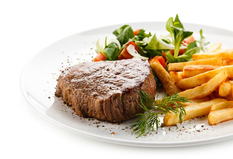 Grilled steak, French fries and vegetables stock images