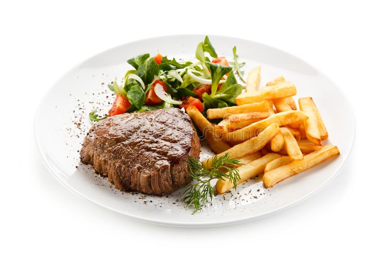 Grilled steak, French fries and vegetables stock image