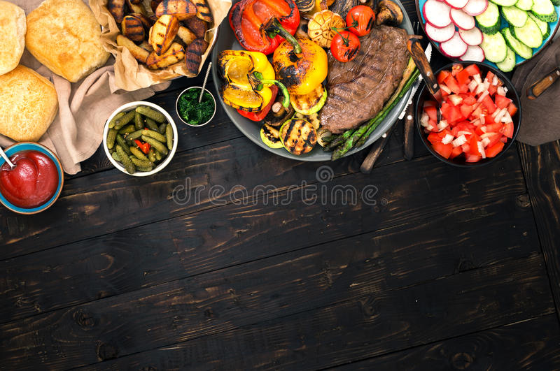 Grilled steak and grilled vegetables on wooden table with border stock photography