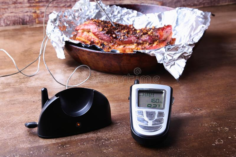 Grilled Steak in a pan and Wireless Remote Digital Cooking Food Probe Meat Thermometer For Grill on a black background. Copy space stock images
