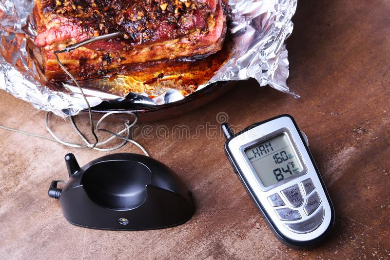 Grilled Steak in a pan and Wireless Remote Digital Cooking Food Probe Meat Thermometer For Grill on a black background. Copy space royalty free stock images